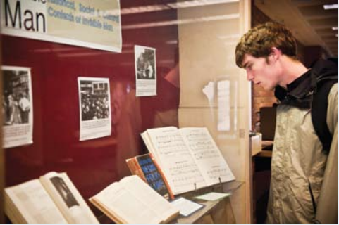 A student takes in a Sawyer Library display about the book's historical, social and cultural contexts.