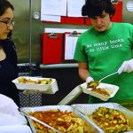 Two students scooping up food from large trays to package for delivery