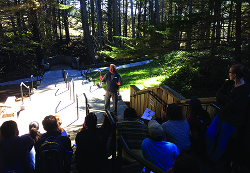 Photo from California of an instructor presenting to a group of students who are sitting in bleachers.