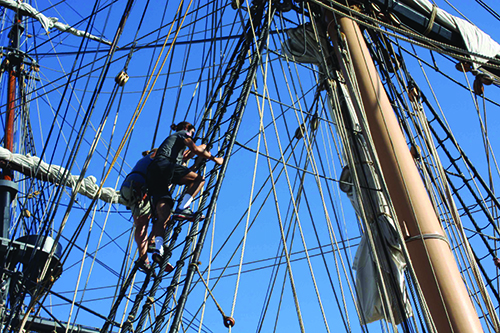 Students climbing the lines of a tall ship.