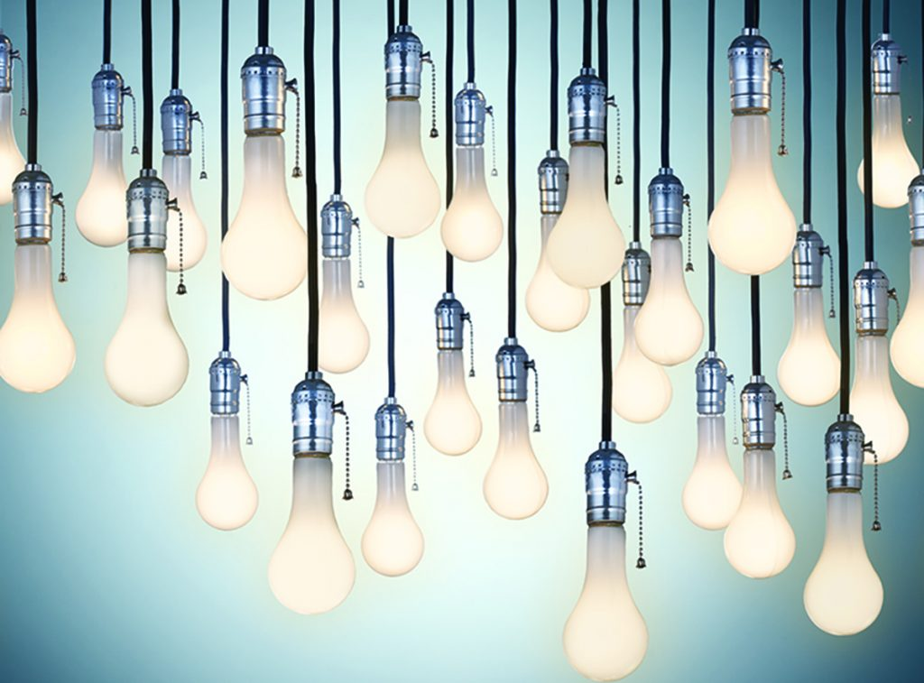 An illustration of many lightbulbs hanging from a ceiling.