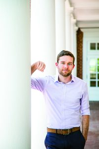 Portrait of Jared Currier, Class of 2009. He leans against a white pillar and is looking at the camera with one hand in his pocket. Short brown hair and short beard.