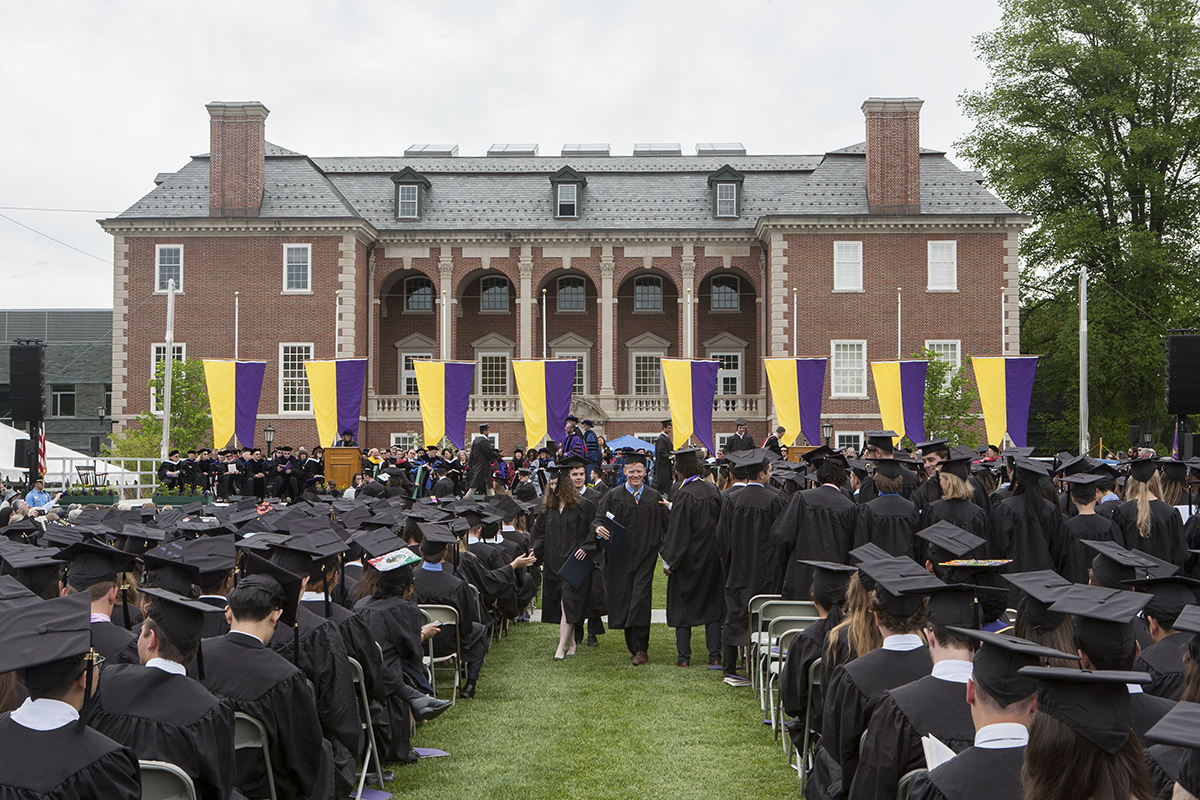 Photo from commencement showing graduates walking back to their chairs after having received their diploma. In the background is Sawyer Library.