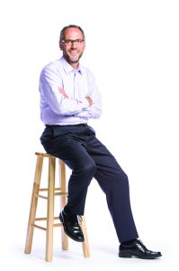 A portrait of Williams president Adam Falk, seated on a stool with arms crossed and looking at the camera.