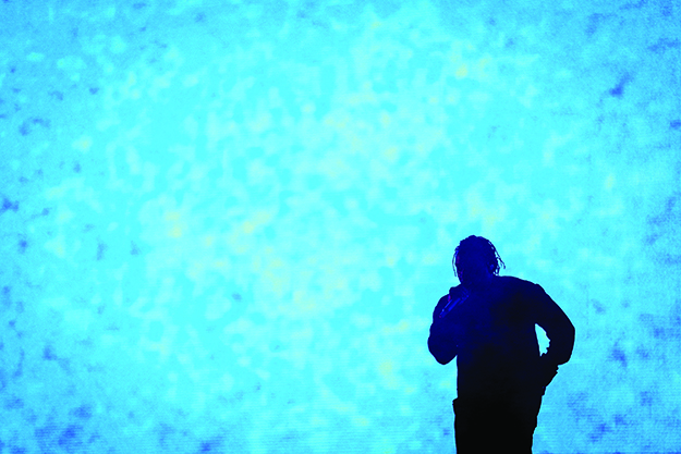 Photograph of Kendrick Lamar performing on stage, mostly silhouetted with a bright blue background behind him.