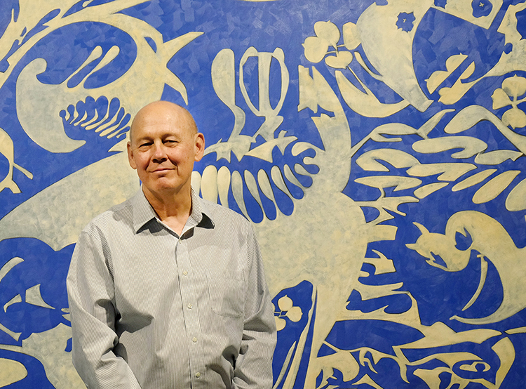 Portrait of art professor Mike Glier who stands in front of one of his paintings.