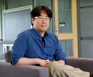 A portrait of economics professor Matt Chao, seated and looking at the camera.