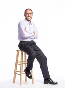 Williams Colllege President Adam Falk sits on a stool, arms crossed on his chest, looking at the camera and smiling.
