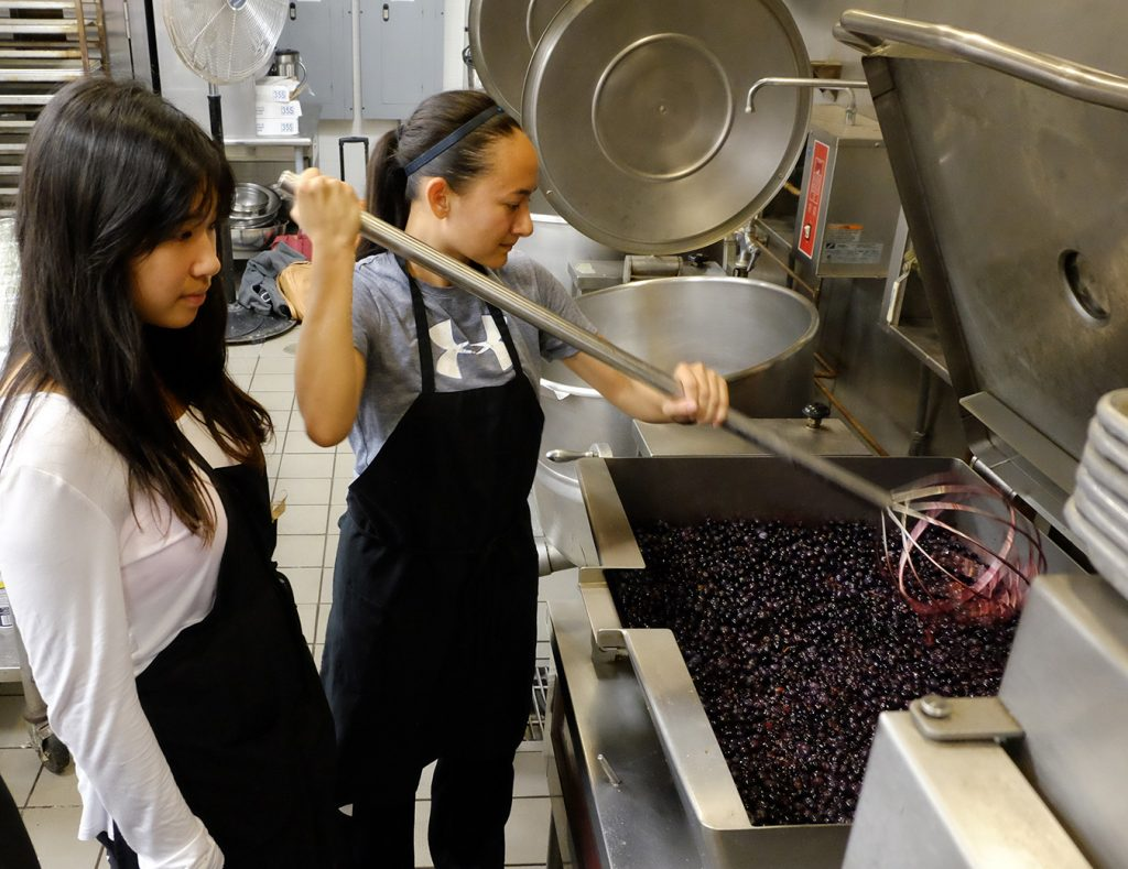 Two female students face an industrial sized cauldron where blueberries boil. One of the students stirs the blueberries.