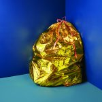 A trash bag made of gold sits in a corner with a royal blue wall and teal floor.