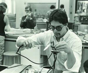 Photo from 1984 of a student in a glassblowing workshop.