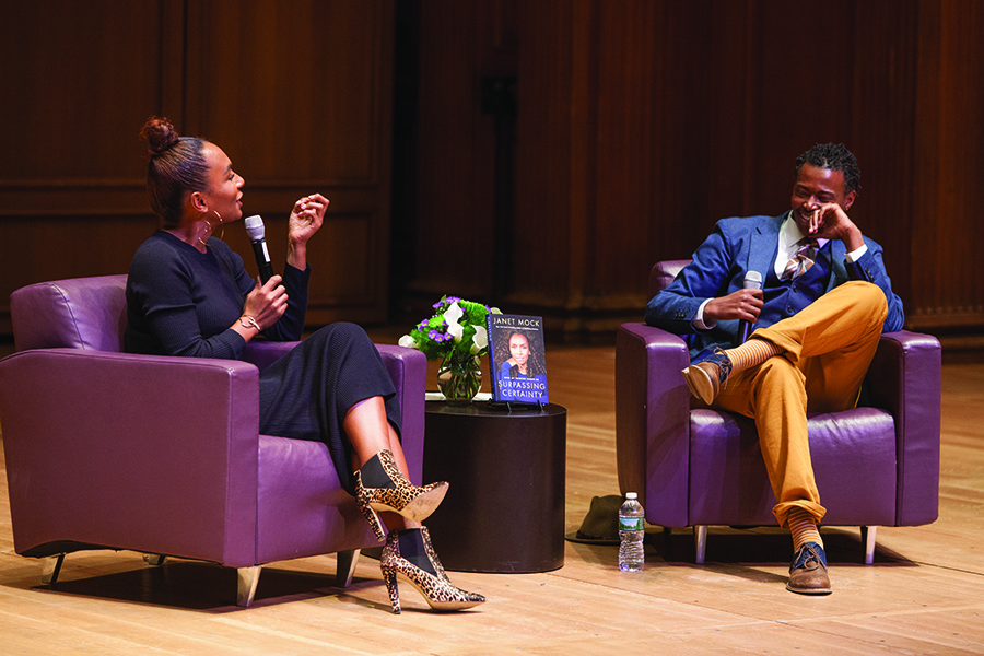 Activist and writer Janet Mock sits on stage with a microphone in her hand, turned toward Professer Kai Green as they chat during Claiming Williams.