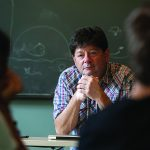 Photo of Professor Shawn Rosenheim sitting at his desk in the front of the classroom, hands clasped under his chin, looking at the students in the class, a chalkboard is behind him.