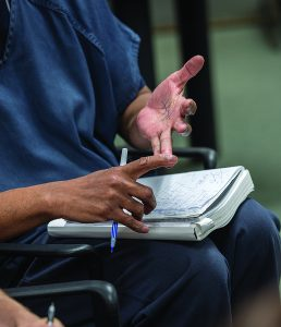 A detail photo of hands with the right pointer finger holding down two fingers from the left hand, as if counting. On the person's lap is a notebook with ink mark. He also holds a pen in his right hand.