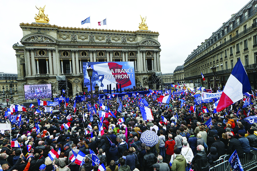 Members and supporters of France's far-right Front National (FN) party hold French flags as they attend a speech by FN president Marine Le Pen on the Place de Opera during the party's annual rally in honor of Joan of Arc on May 1, 2015 in Paris.
