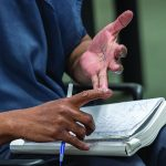 Detail of a man's hands as he uses them to gesture over his notebook.
