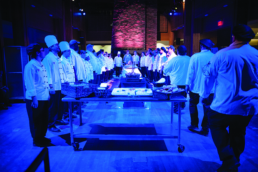 Staff from dining services form a U-shape around tables while bathed in blue light from above. The staff performed as part of Served, a show based on their everyday movements.