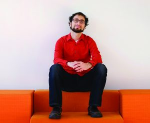 A portrait of Zaid Adhami. Dark hair, beard, glasses, wearing an orange button down shirt and black pants and sitting on an orange couch. A white wall is behind him and he looks straight at the camera, hands clasped in front of him.