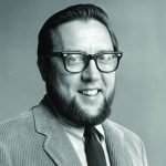 Headshot of deceased professor Thomas McGill—he dons glasses, a beard, corduroy jacket and dark tie and smiles at the camera.
