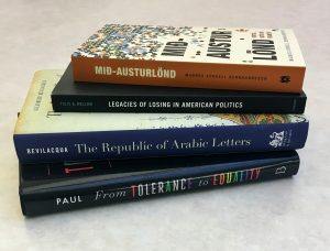 A photo of four books stacked on a table.
