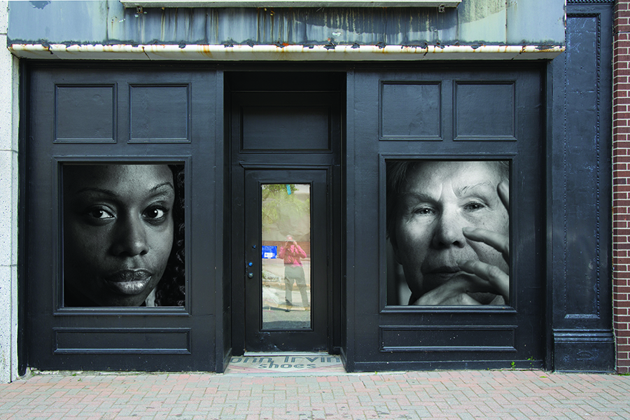 Photo of two large portraits in the windows of a building with a reflection of the photographer in the glass of the door.
