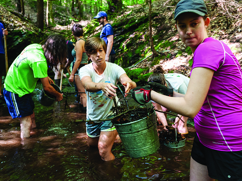 A photo of volunteers clearing debris out buckets of debris from streams in Hopkins Forest.