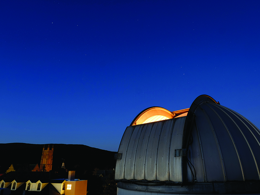 Night time photo of observatory with campus in background.