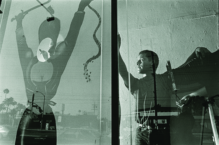 Photo showing Simon Doonan (left) and Mundo Meza (right) working in the window of Maxfield Bleu.