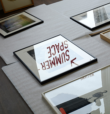 "Photograph of art pieces on the floor with the words ""summer space"" reflected in the glass of one."
