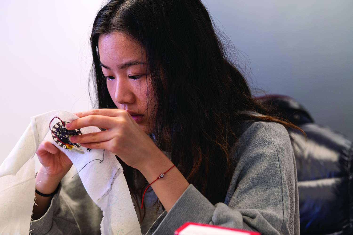 Photo of a student sewing electronics into a piece of cloth