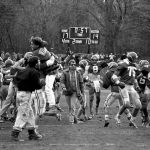 Black and white photo of Coach Dick Farley walking through his players as they celebrate a win.