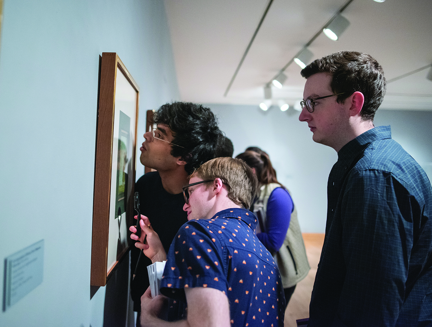 Photo of students closely inspecting a piece of art on the wall at WCMA.