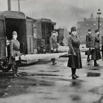 St. Louis Red Cross Motor Corps on duty Oct. 1918 Influenza epidemic. Photograph shows mask-wearing women holding stretchers at backs of ambulances.