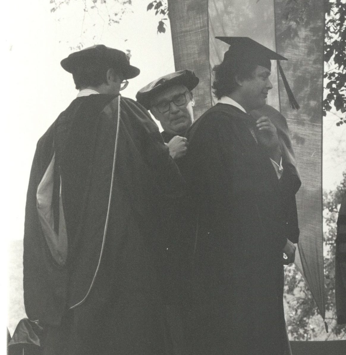 A man receives an honorary degree in an outdoor ceremony.