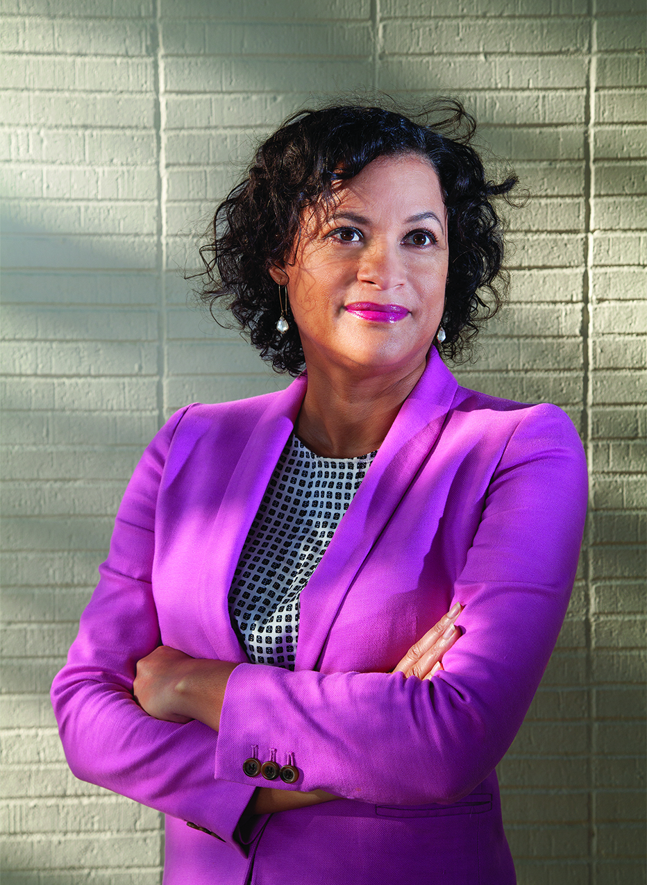 Photograph of woman wearing a fuschia blazer with arms crossed.