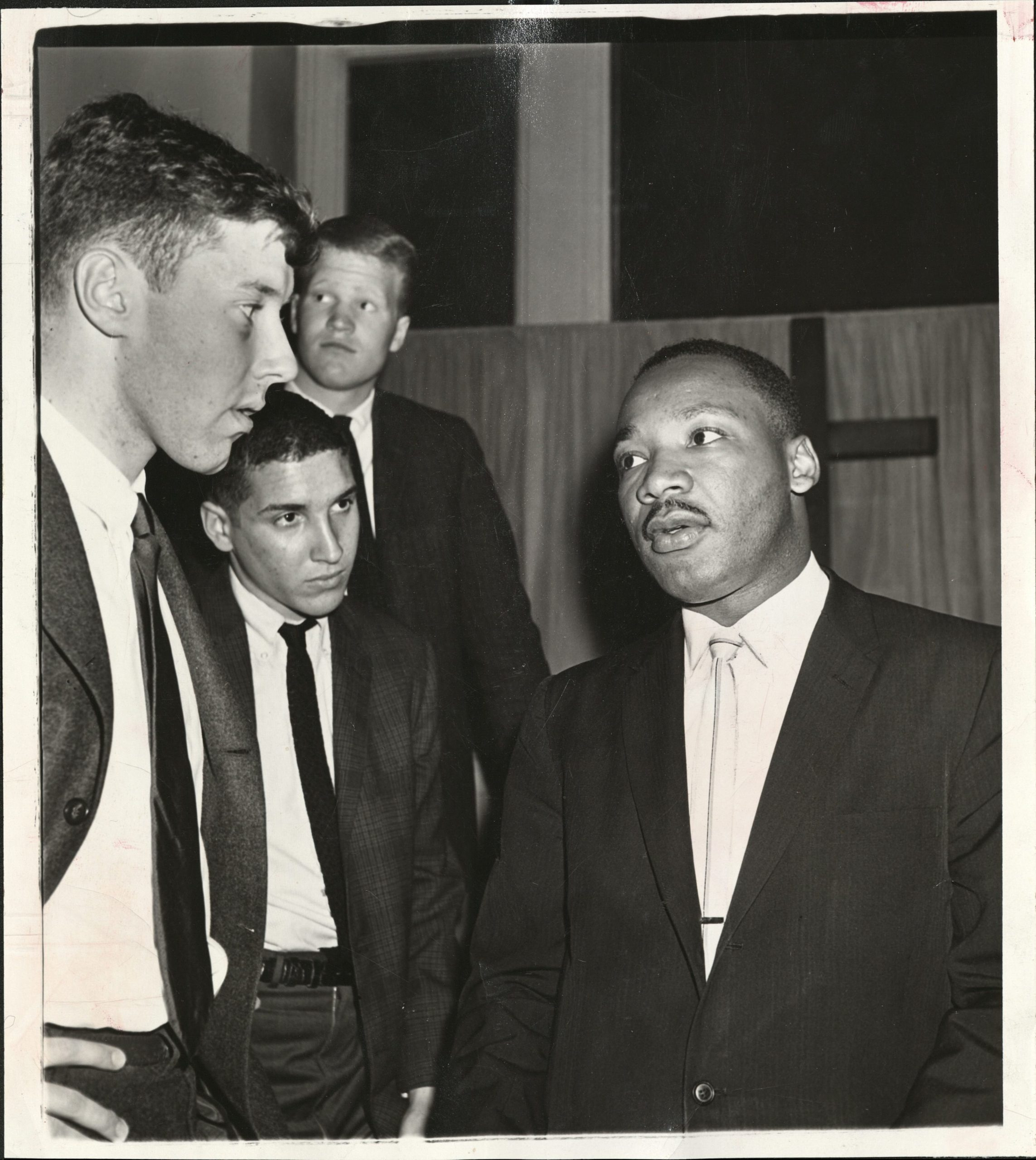 Martin Luther King, Jr. talk with three young men.