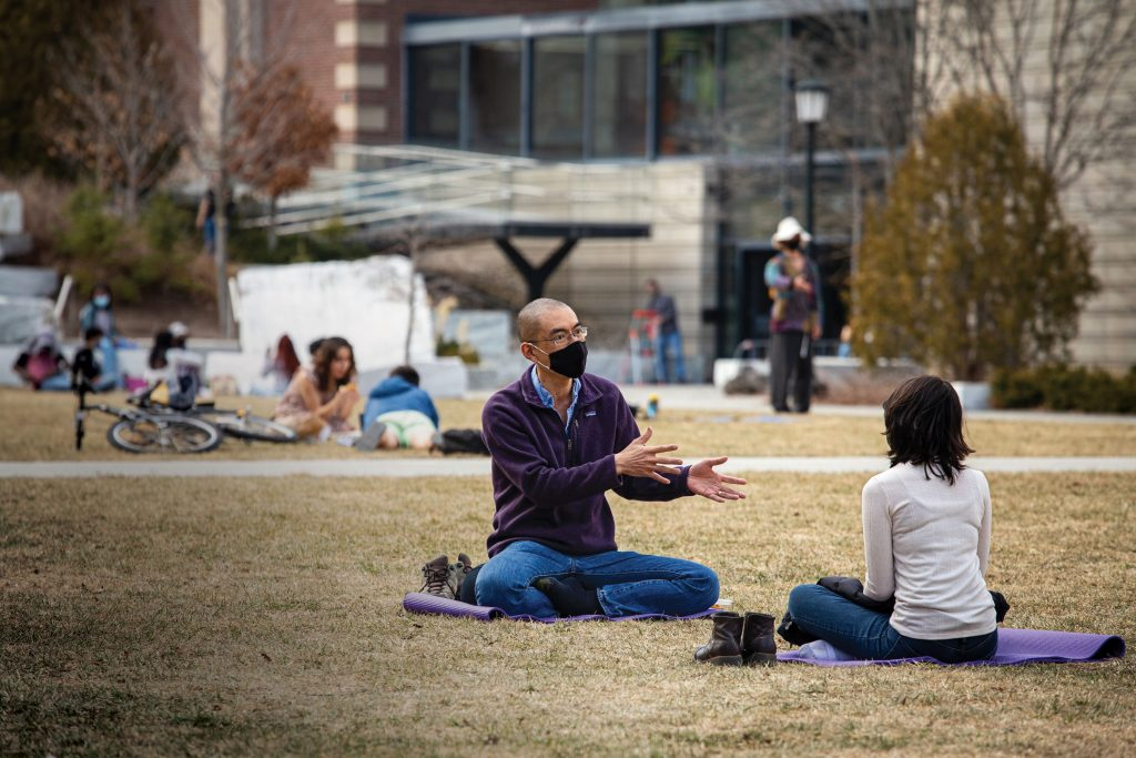 Two people sitting on the grass and talking with masks on
