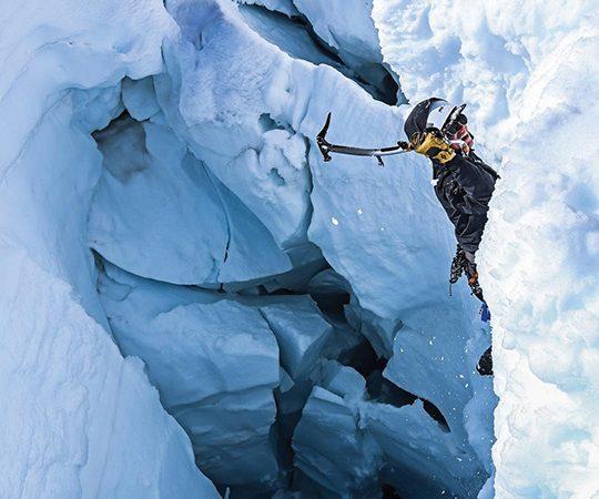 Photo of Bertie Miller climbing an ice crevasse