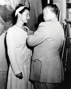 A man is pinning an award on a woman's lapel.